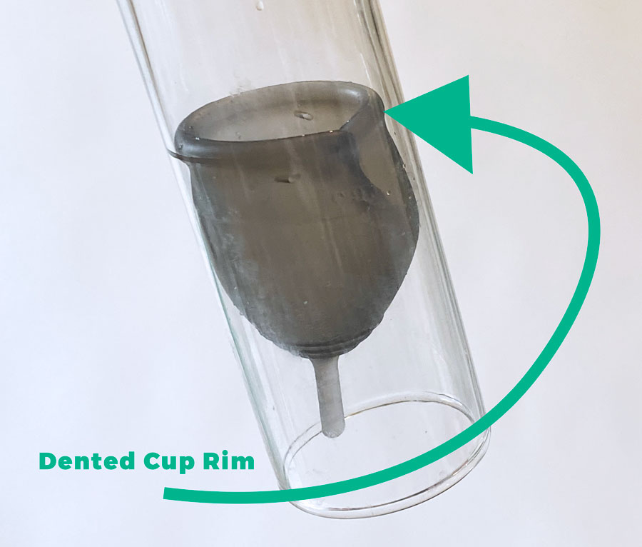 grey menstrual cup that's leaking - dented cup rim in a clear tube